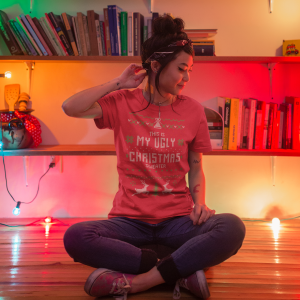 girl sitting next to christmas lights and bookshelves wearing a round neck t shirt mockup a17780 copy