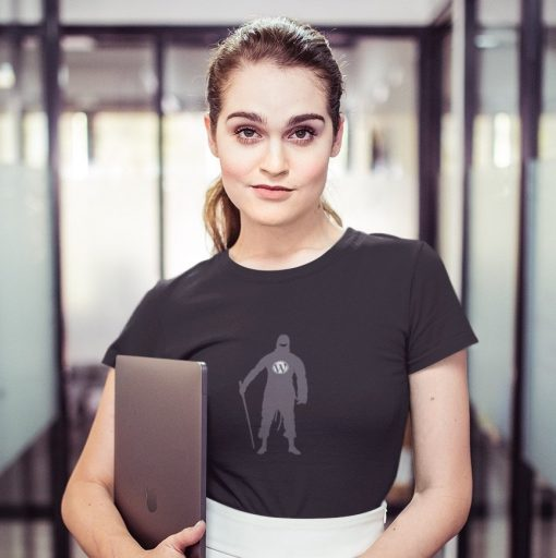 woman wearing a tshirt mockup holding a laptop in a corridor at the office a20516